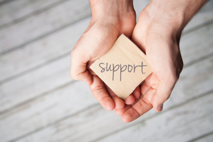 picture of a person holding a piece of paper that says support