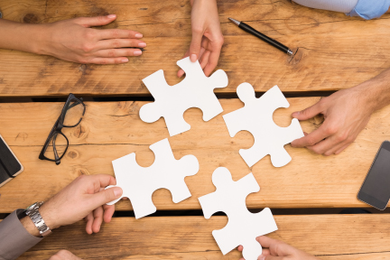 A picture of people putting together a puzzle.