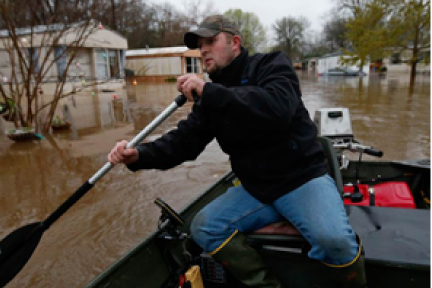 Picture of a person riding a small boat down a flooded street