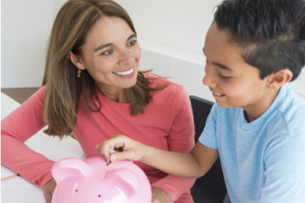picture of a child putting money into a piggy bank