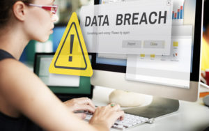 Picture of woman looking at computer with data breach popup window