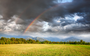 Picture of Rainbow under grass field, trees and mountains at dramatic storm sky with dark clouds background
