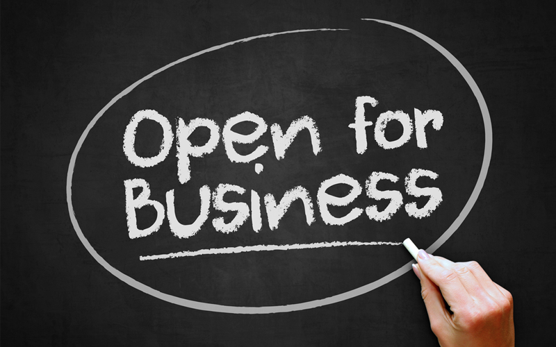 Picture of hand writing 'Open for Business' on chalkboard.