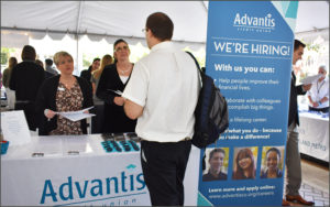 Job fair attendee visits with employees from Advantis Credit Union.
