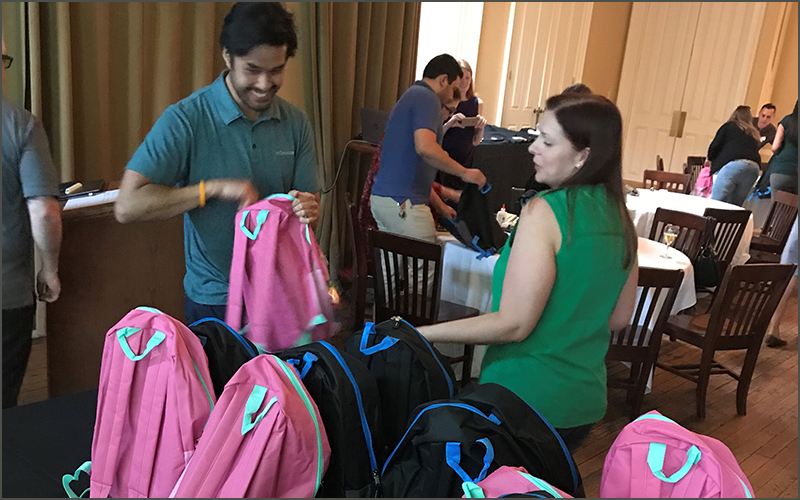 People fill pink backpacks with school supplies.
