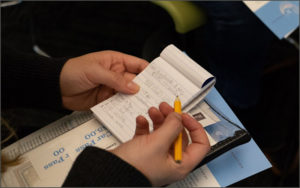 Close up image of man holding a notebook and pencil