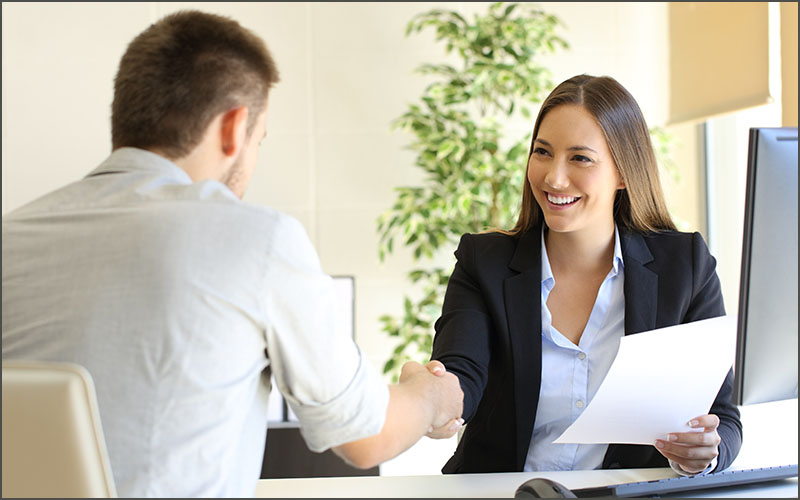 Woman at desk shaking hands with man