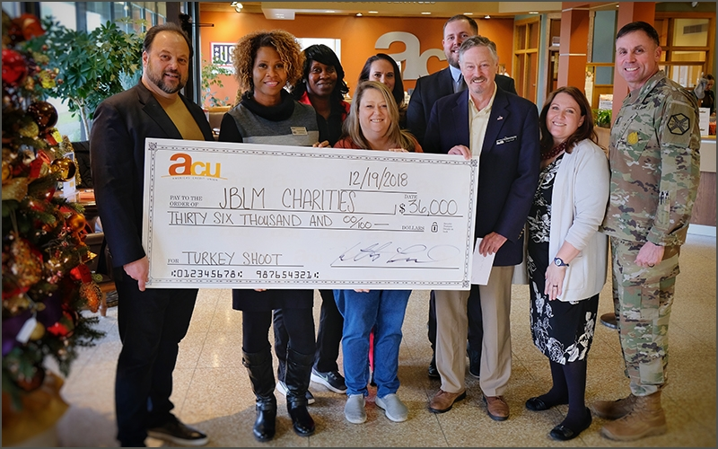People standing with a donated check